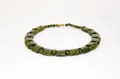 Una collana del diaspro verde su un fondo bianco Immagine Stock