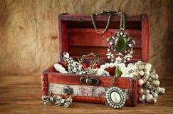 Una collezione di gioielli d'annata in contenitore di gioielli di legno antico immagini stock
