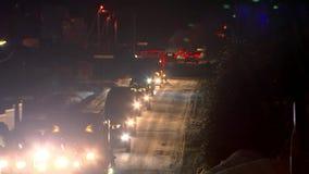 Una colonna di guida di veicoli alla notte su una strada di inverno Abbagliamento dai fari video d archivio