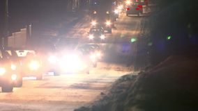 Una colonna di guida di veicoli alla notte su una strada di inverno Abbagliamento dai fari archivi video