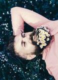 Una com o conceito da natureza O homem farpado com flores da margarida coloca no grassplot, fundo da grama Homem com a barba no s fotos de stock
