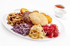 Una comida sabrosa. Hamburguesa grande, patatas fritas.   Imágenes de archivo libres de regalías