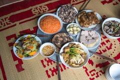 Una comida vietnamita tradicional para el día de fiesta lunar de Tet del Año Nuevo en primavera, puesta en la nueva estera florec Imágenes de archivo libres de regalías