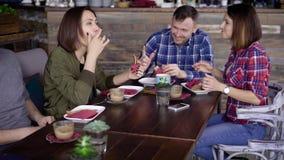 Una compañía adulta de amigos está comiendo los bocadillos deliciosos con los pescados y las verduras, bebiendo el café con leche metrajes