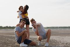 Una compañía de adolescencias que camina en un riverbank, muchachos que toman un selfie, muchachas que abrazan en un fondo borros Fotos de archivo libres de regalías