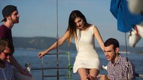 Una compañía de amigos jovenes y modernos está colgando hacia fuera en un yate en el verano metrajes