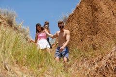 Una compañía de amigos sonrientes desciende de la colina cerca de una costa en un fondo natural Imagenes de archivo