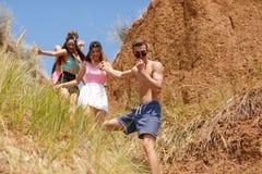 Una compañía de amigos sonrientes desciende de la colina cerca de una costa en un fondo natural Imagen de archivo libre de regalías