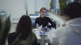 Una compañía de la gente joven está descansando en un restaurante o un café acogedor agradable que come los platos deliciosos par metrajes