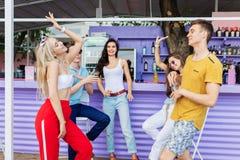 Una compañía de los amigos apuestos que ríen, de los cócteles amarillos de consumición, bailando y socializando en la barra en el fotografía de archivo