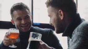 Una compañía de los amigos masculinos hermosos que tienen conversación, son de risa, humorísticos, que tuestan y de consumiciones almacen de video