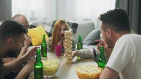 Una compa??a de amigos juega una torre de madera en una sala de estar acogedora metrajes