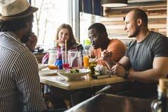 Una compa??a de la gente joven multicultural en un caf? que come la pizza, c?cteles de consumici?n, divirti?ndose foto de archivo libre de regalías