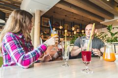 Una compa??a de la gente joven que se divierte, bebidas de consumici?n, c?cteles, jugos en un caf? mejores amigos de la reuni?n imagen de archivo