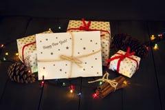 Una composición con los regalos del ` s del Año Nuevo y un sobre con la tarjeta de felicitación de la Feliz Año Nuevo de la inscr Fotos de archivo libres de regalías