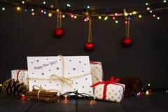 Una composición con los regalos del ` s del Año Nuevo y un sobre con la tarjeta de felicitación de la Feliz Año Nuevo de la inscr Foto de archivo