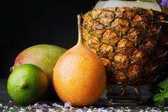 Una composición de las frutas del verano Frutas cítricas coloridas y una taza de la piña Mango, cal, y pomelo en un fondo negro Fotografía de archivo libre de regalías