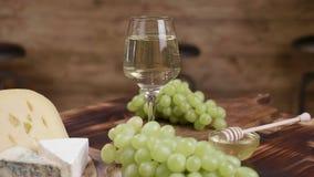 Una composición de quesos y de un vidrio de vino blanco en el centro almacen de video