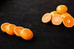 Una composición del corte en naranjas y mandarinas de las mitades en un fondo negro Foto de archivo