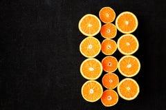 Una composición del corte en naranjas y mandarinas de las mitades en un fondo negro Fotografía de archivo