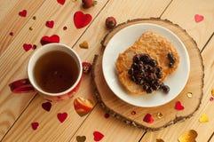 Una composición rústica acogedora con una taza de té roja, una placa de crepes con el atasco, y los corazones decorativos en una  Imagen de archivo libre de regalías