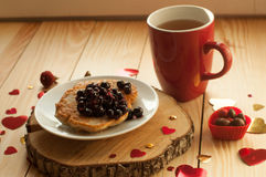 Una composición rústica acogedora con una taza de té roja, una placa de crepes con el atasco, y los corazones decorativos en una  Fotografía de archivo libre de regalías