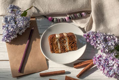 Una composizione con un pezzo di dolce di cioccolato, una carta e una matita, i fiori lilla e una collana Fotografia Stock