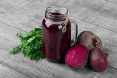 Una composizione degli ingredienti sani Barattolo della bevanda della barbabietola su un fondo grigio Succhi della verdura per i  Fotografia Stock Libera da Diritti