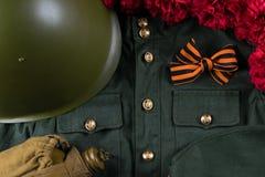 Una composizione dei fiori rossi, di un casco verde, di una bottiglia militare e di una forma con un nastro da Fotografie Stock Libere da Diritti