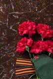 Una composizione dei fiori rossi, di un nastro di St George e di un cappuccio militare con una stella sui precedenti di marmo Immagini Stock