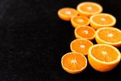 Una composizione del taglio in arance e mandarini di metà su un fondo nero Fotografia Stock