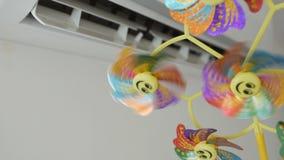 Una condizione adulta dell'uomo davanti al condizionatore d'aria che tiene un giocattolo dei bambini con un'elica girante video d archivio
