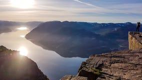 Una condizione dell'uomo sulla roccia famosa di Preikestolen in Norvegia L'alba sta avendo luogo sopra il fiordo immagini stock libere da diritti
