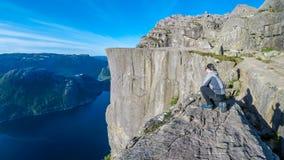 Una condizione dell'uomo sulla roccia famosa di Preikestolen in Norvegia fotografia stock