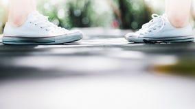 Una condizione della scarpa da tennis di usura delle coppie si confronta lungo la strada della passeggiata, concetto di amore Fotografie Stock Libere da Diritti