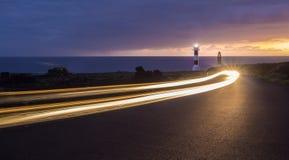 una conducción de automóviles delante de un faro en la puesta del sol fotografía de archivo libre de regalías
