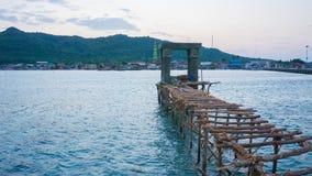 Una construcción de la cubierta de madera en el mar azul con la isla grande como fondo fotografía de archivo