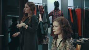 Una conversazione dello stilista della ragazza del trucco di sera nel boutique dell'abbigliamento del ` s delle donne stock footage