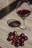 Una copa con el vino rojo y las cerezas en fondo de madera con las sombras Fotografía de archivo libre de regalías