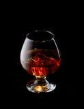 Una copa de vino con los cubos del whisky y de hielo en un fondo negro Imagen de archivo