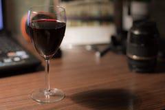 Una copa de vino en el escritorio imagenes de archivo