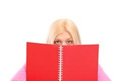 Una copertura femminile impaurita dietro il libro Immagine Stock