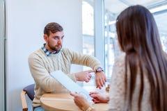 Una coppia ad una data in un caffè, il tipo indica all'orologio, indignato che la ragazza era in ritardo fotografie stock