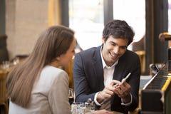 In una coppia allegra del ristorante che pratica il surfing il web, guardante un phot fotografie stock