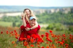 Una coppia amorosa sta divertendosi in un campo con i fiori del papavero fotografia stock libera da diritti