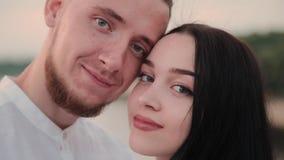 Una coppia amorosa sta stando su un ponte contro un cielo blu archivi video