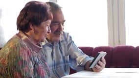 Una coppia anziana comunica con il loro nipote dal video che collega la compressa Un uomo e una donna stanno parlando con stock footage