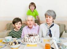 Una coppia anziana sta spegnebbi le candele su un dolce Fotografia Stock