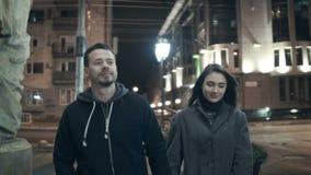Una coppia cammina a partire dalla macchina fotografica alla notte mentre cammina le vie della città stock footage