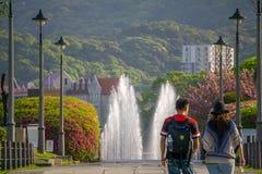 Una coppia che cammina giù una via di pietra verso una fontana Fotografie Stock